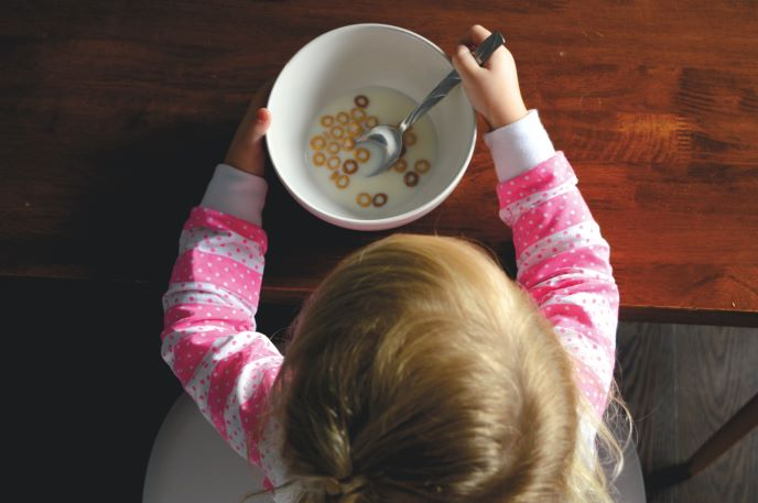 Toddler eating cereal at the table